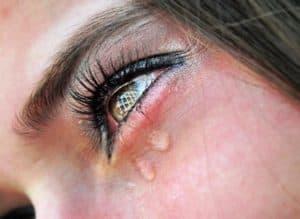 У девушки текут слезы